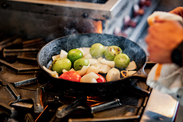 Tomatillos cooking in cast-iron pan with onion