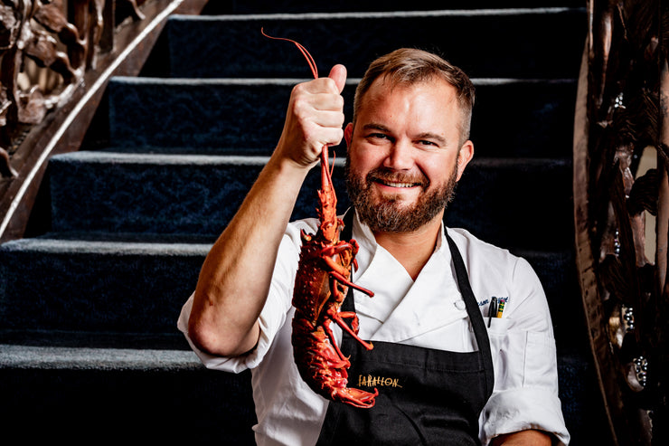 Chef holding spiny lobster by stairway
