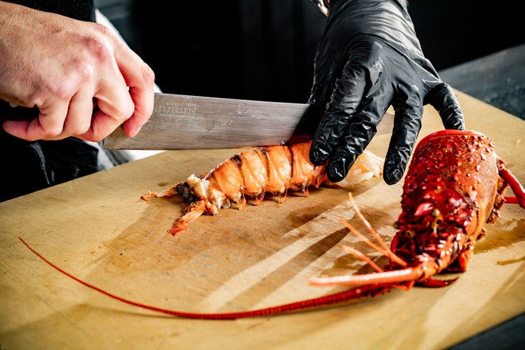 chef hands slicing spiny lobster tail