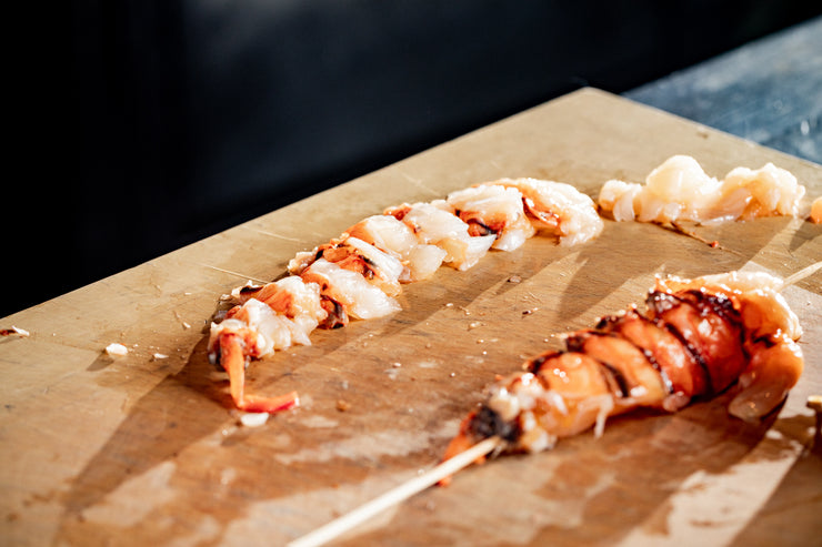 Sliced lobster tails on cutting board