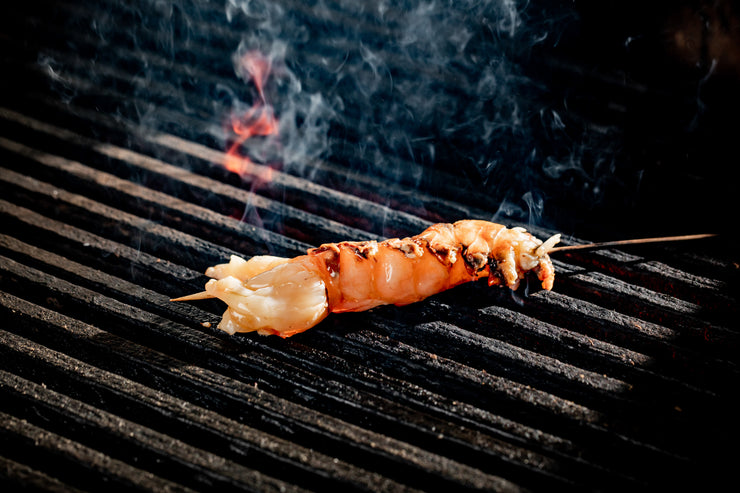 Spiny lobster tail skewer on grill with fire smoking