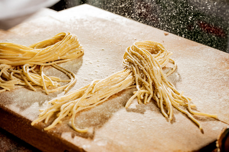 flour falling on fresh pasta on a cutting board in the kitchen