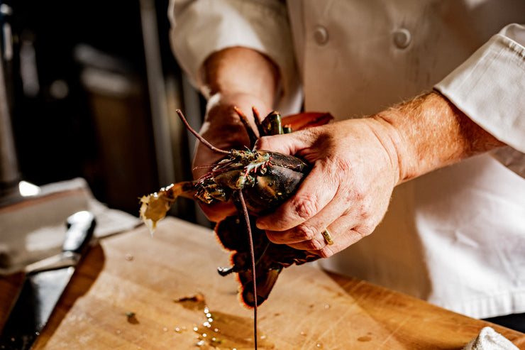 chef hands separating lobster claws from the body