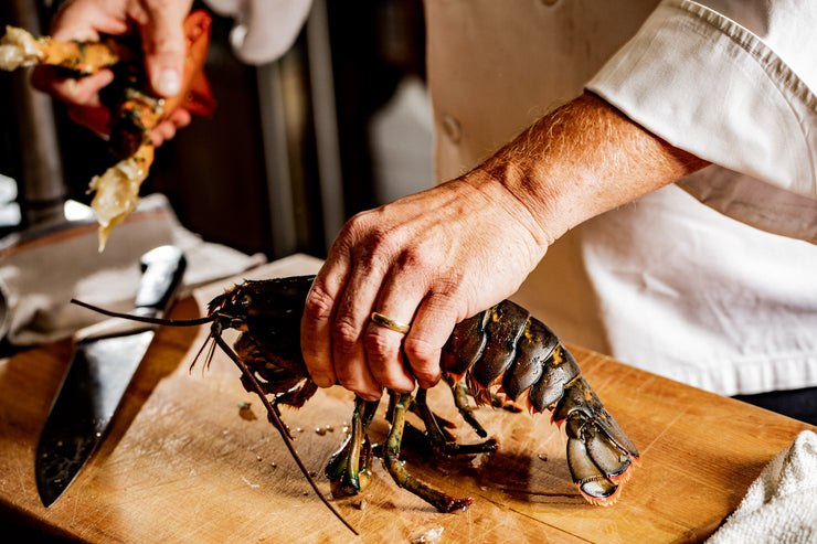 chef hands holding lobster while setting aside claws