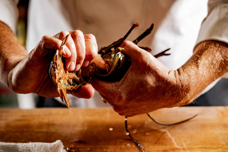 chefs hands twisting lobster tail