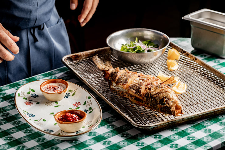 Whole fried Branzino sitting on a rack on a picnic table