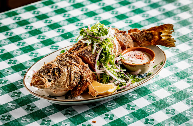 Whole Fried Branzino with salad on green picnic table