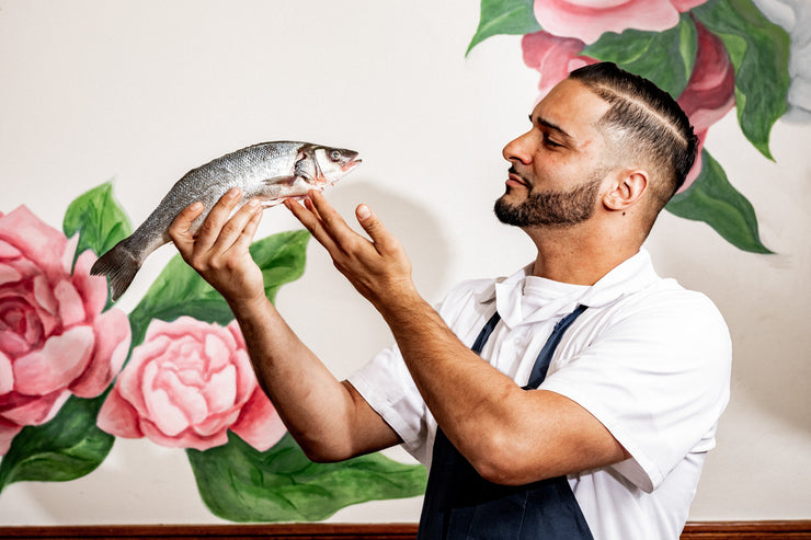 Chef examining fish in front of flower wallpaper