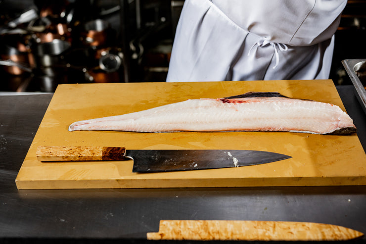 Black cod on cutting board with knife