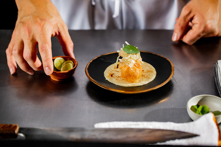 Chef hands plating fish taco and lime