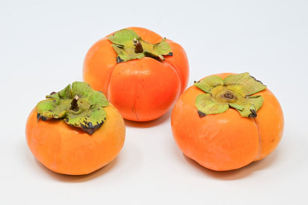 three fuyu persimmons in a triangle
