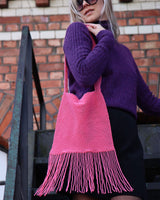 the Marmaclub Crossover Fringe Hot Pink on model in purple sweather and black skirt in a steep stair ers in front of a red wall
