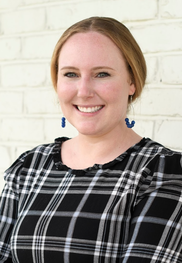 Headshot of Shelley Evans in a black and white striped plaid shirt, smilling, sunny day with a painted white brick wall background