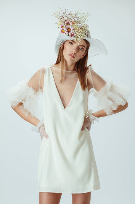 Model wears ivory mini dress with flower hat on her head