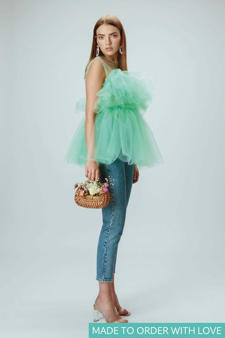 Model is wearing mint green tulle top holding a flower basket