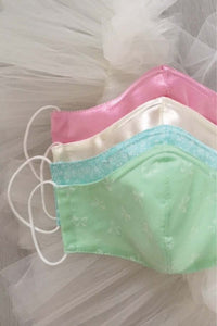 4 face masks one in mint, one in aqua, one in ivory satin and one in pink satin on a bed of tulle