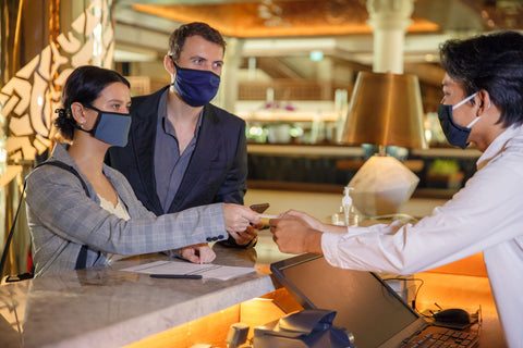 Guest with PPE face masks checking into a premium hotel