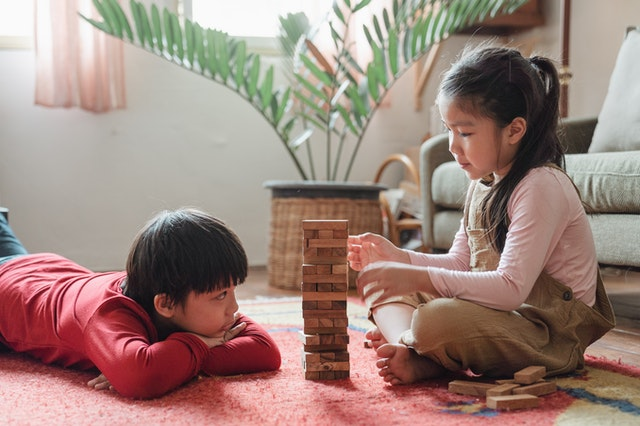 Children playing with a wooden block tower on the floor