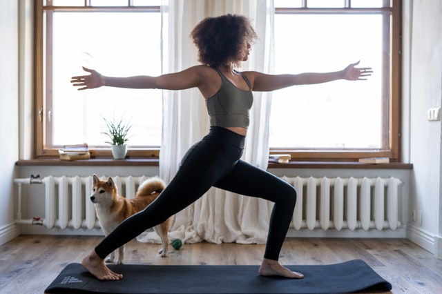 Woman practicing yoga at home with a dog