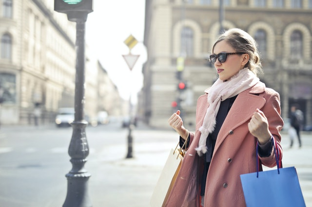 Woman in a pink coat wearing sunglasses and a scarf holding shopping bags