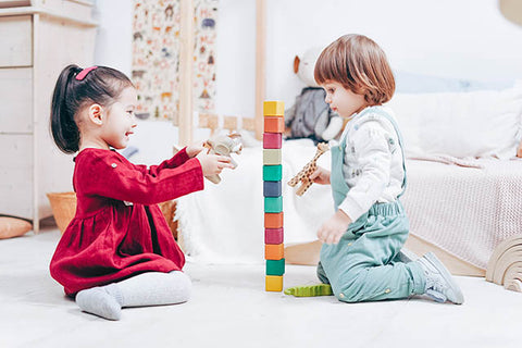 Two young friends sharing toy blocks