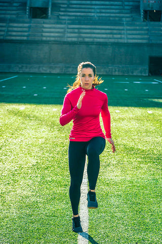 Woman doing high knee drills outside on football field