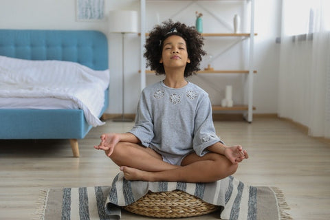 Young girl meditating in room