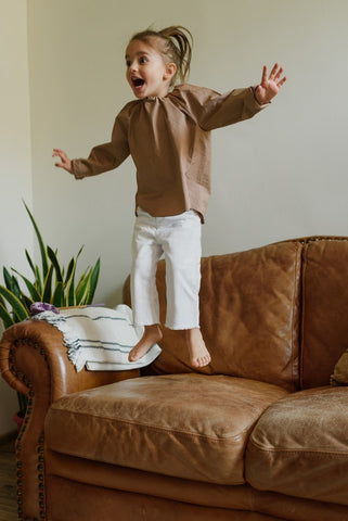 Little girl jumping on the couch