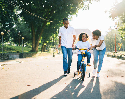 Parents teaching child how to ride a bicycle