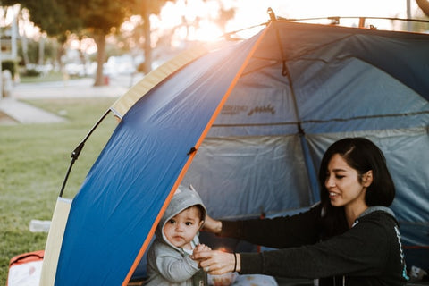 Mother and young son camping out inside the tent