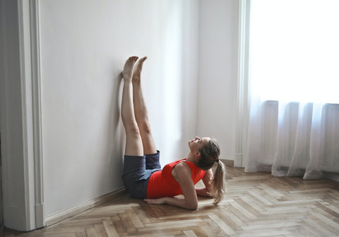 Woman lying on the floor with her legs on the wall