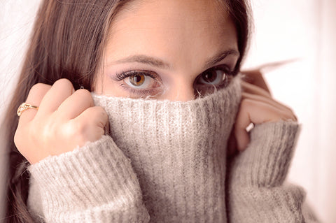 Woman covering face with sweater