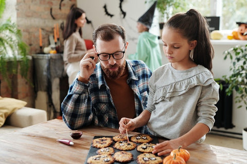 Father and daughter decorating Halloween cookies
