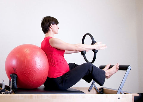Woman exercising with exercise ball and workout machine