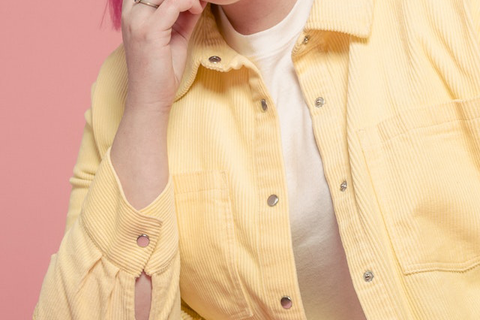 Pink-haired woman wearing yellow corduroy shacket