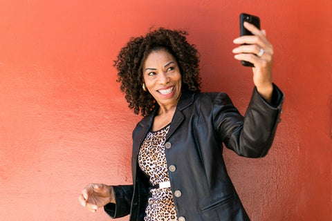 Woman holding phone while wearing leather shacket