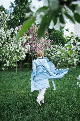 Woman in a blue coat and white pants in a garden with blooming trees