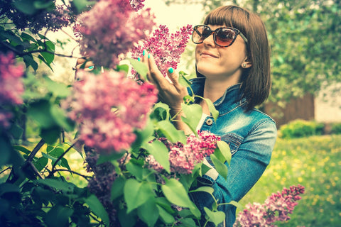 Woman wearing suglasses and a jean jacket holding lilac flowers