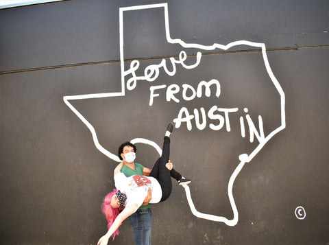 """Cate (she/her) being dipped by Darwin (he/him) in front of a mural that says """"Love from Austin"""""""