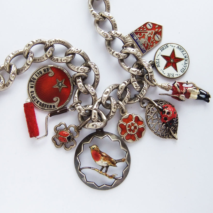 A collection of red themed antique and vintage bracelet charms | Silver Star Charms