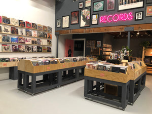 Interior view of Rust & Wax Record Shop in West Palm Beach, FL, showing the main floor with record bins, record wall, and small merchandise items for sale.