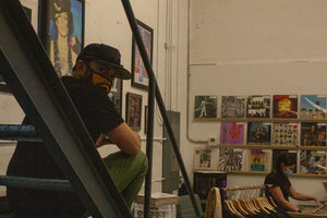 Image of Rust & Wax Record Shop owners, Melanie & Jesse Feldman, behind the counter of the shop.