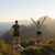 Man and Women Hiking on top of mountain while women has her hands up