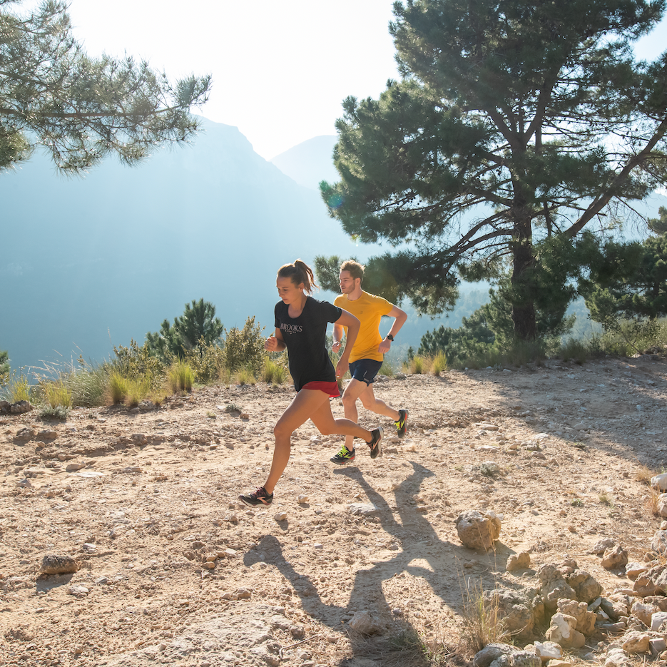 Woman and man running on a trail on the side of a mountain