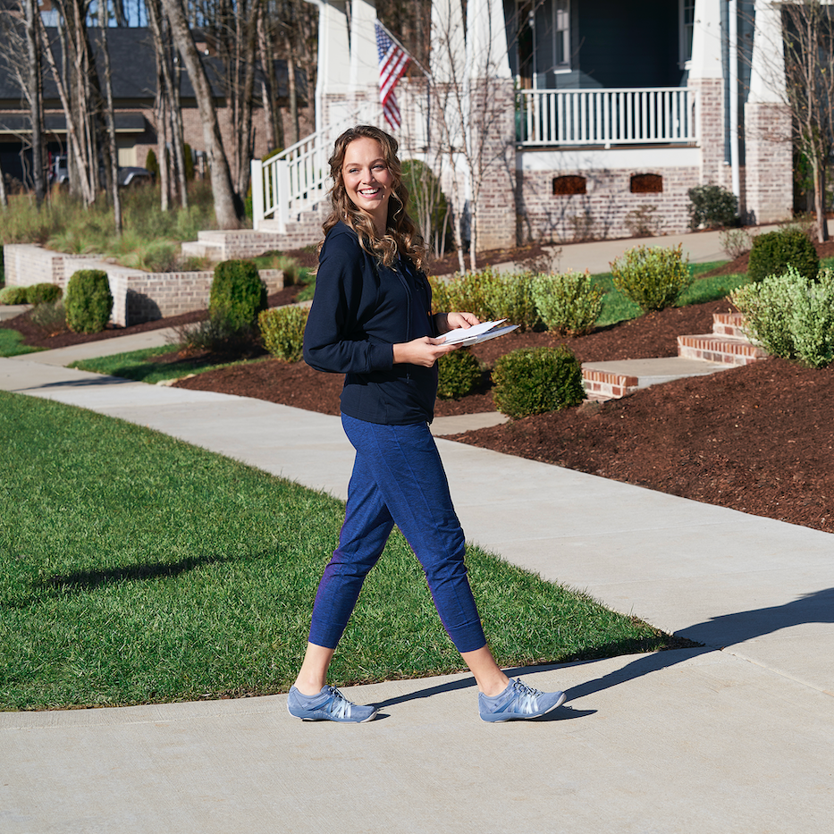 A women in walking shoes walking on the side walk in a neighborhood with mail in her hands