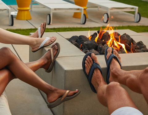 Family wearing Vionic Flip Flops around a fire by a pool