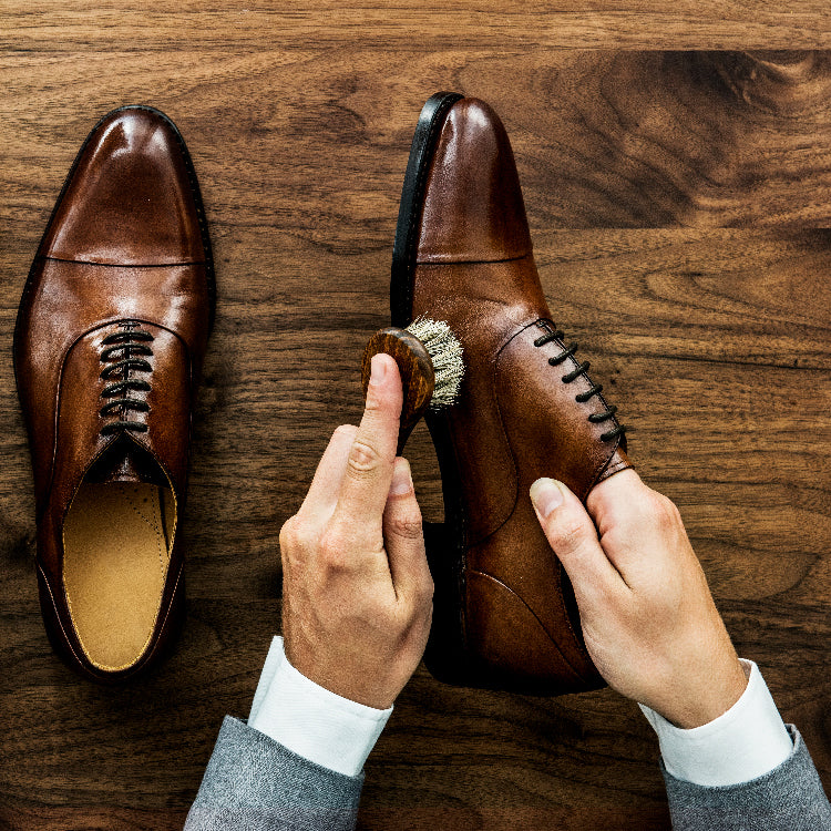 Links to all Shoe Care Accessories - man cleaning dress shoes with a brush on a wooden table