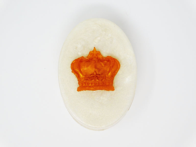 White oval soap with a gold crown on top. Soap that smells like cherry blossoms and rosé
