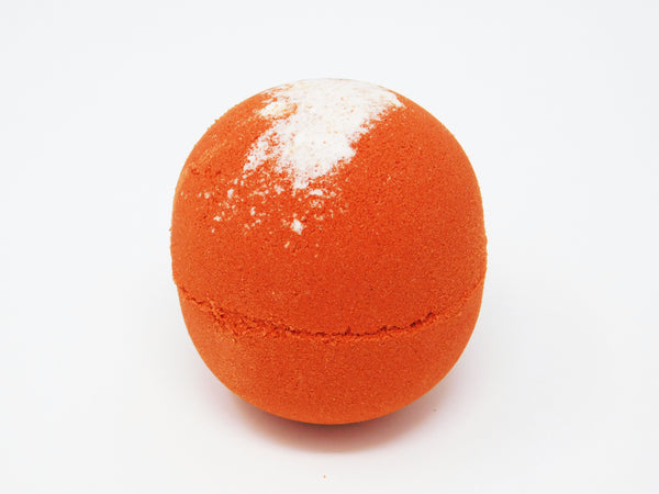 Round red bath bomb made with coconut oil, coconut milk powder, and blood orange essential oil.