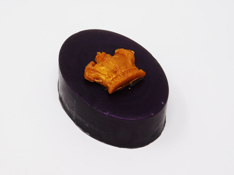 Dark purple oval shaped soap with a gold crown on top. Soap that smells like heliotrope blossoms and oud incense